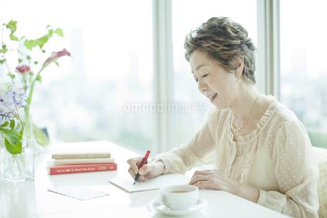リビングで手紙を書く中高年女性の写真素材 [FYI01624418]