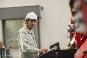 機械を操作する作業服の男性の写真素材 [FYI01624426]