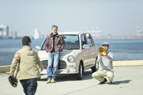 海岸でキャッチボールをするシニア男性の写真素材 [FYI01624428]