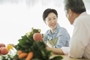 野菜を持って笑顔のシニア夫婦の写真素材 [FYI01624430]