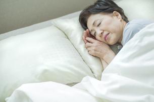 ベッドで眠るシニア女性の写真素材 [FYI01624432]
