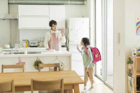 キッチンに立つ母親とランドセルを背負った女の子の写真素材 [FYI01624451]