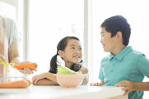 キッチンで料理をする母親に寄り添う子供たちの写真素材 [FYI01624483]