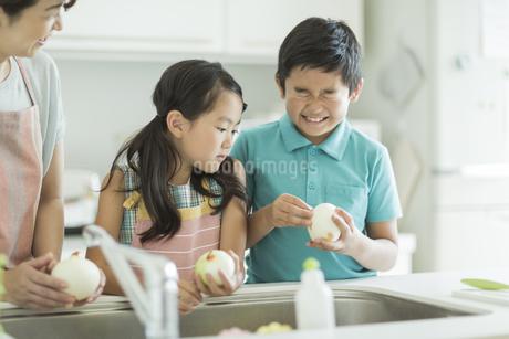 キッチンで玉ねぎの皮を剥く兄と妹の写真素材 [FYI01624484]