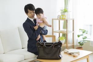 出勤前に赤ちゃんを抱っこする父親の写真素材 [FYI01624496]