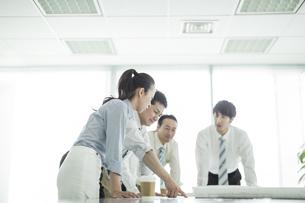 テーブルに図面を広げて打ち合わせをするビジネスマンとビジネスウーマンの写真素材 [FYI01624502]