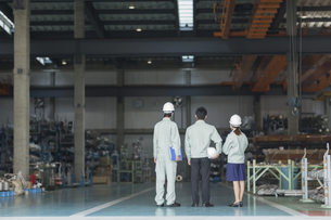 工場で立つ男女作業員の後姿の写真素材 [FYI01624505]