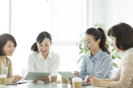 テーブルで打ち合わせをするビジネスウーマンの写真素材 [FYI01624509]
