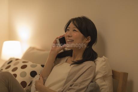 ベッドに座って電話をする女性の写真素材 [FYI01624510]