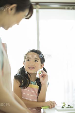 母親に切った野菜を見せる女の子の写真素材 [FYI01624519]
