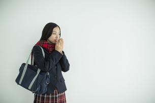息で手を温める女子高校生の写真素材 [FYI01624524]
