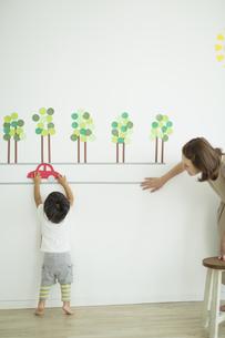 壁のイラストの前で遊ぶ親子の写真素材 [FYI01624532]