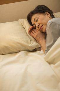 ベッドで眠るシニア女性の写真素材 [FYI01624535]