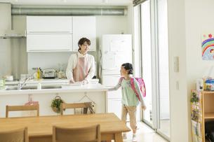 キッチンに立つ母親とランドセルを背負った女の子の写真素材 [FYI01624539]