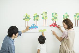 壁のイラストの前の3人家族の写真素材 [FYI01624544]