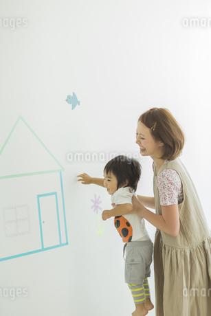 壁のイラストの前で遊ぶ親子の写真素材 [FYI01624545]