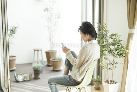 窓辺に座って携帯電話を見る女性の写真素材 [FYI01624546]
