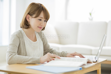 部屋で勉強をする若い女性の写真素材 [FYI01624550]