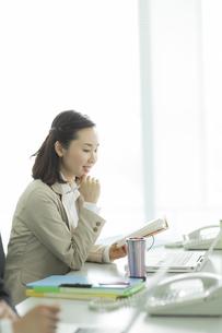 オフィスデスクで手帳を持つビジネスウーマンの写真素材 [FYI01624569]
