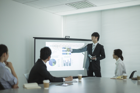 プロジェクターを使用した会議で説明をするビジネスマンの写真素材 [FYI01624583]