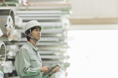 タブレットPCを操作する作業員男性の写真素材 [FYI01624584]