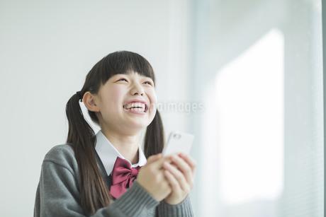 スマートフォンを持って笑顔の女子中学生の写真素材 [FYI01624594]