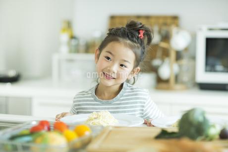 キッチンで微笑む女の子の写真素材 [FYI01624607]