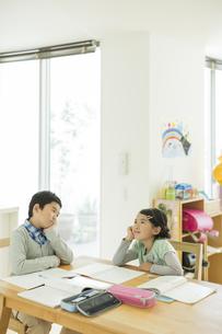 テーブルで勉強をする兄と妹の写真素材 [FYI01624613]