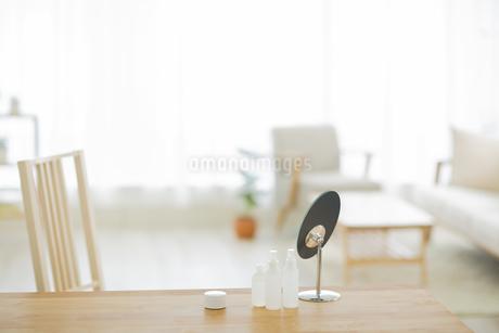 テーブル置かれた化粧品と鏡の写真素材 [FYI01624620]
