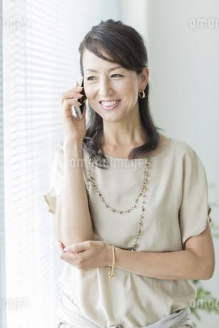 スマートフォンで話すビジネスウーマンの写真素材 [FYI01624621]