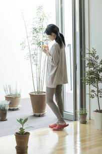 窓辺でコーヒーを飲む若い女性の写真素材 [FYI01624627]