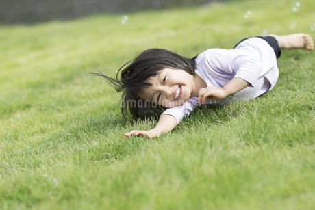 芝生で寝転ぶ女の子の写真素材 [FYI01624628]