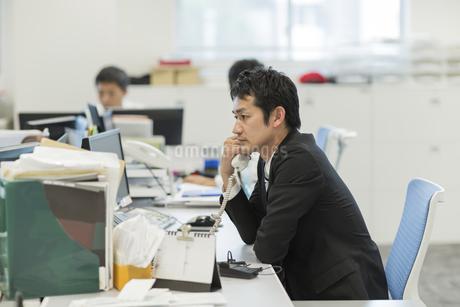デスクで電話をするビジネスマンの写真素材 [FYI01624640]