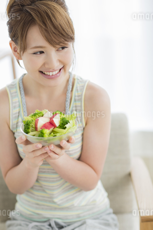 サラダを持って笑顔の若い女性の写真素材 [FYI01624641]