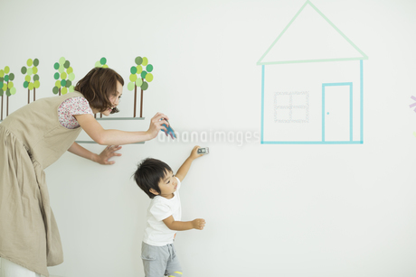 壁のイラストの前で遊ぶ親子の写真素材 [FYI01624644]