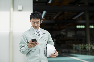スマートフォンを操作する作業着の男性の写真素材 [FYI01624663]