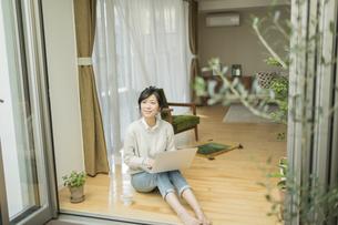 窓辺で外を見上げる若い女性の写真素材 [FYI01624669]