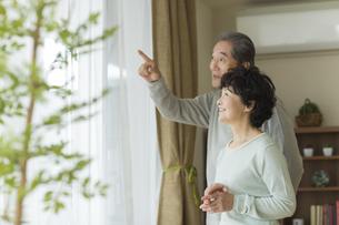 窓辺に立ち外を眺めるシニア夫婦の写真素材 [FYI01624673]