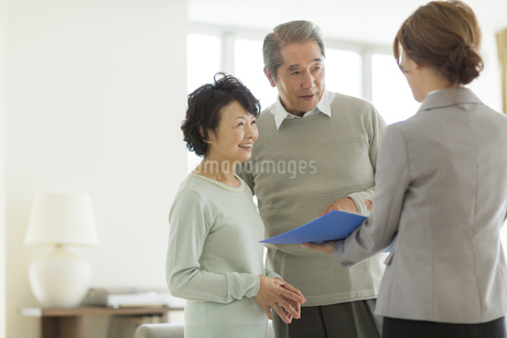 ビジネスウーマンから説明を聞くシニア夫婦の写真素材 [FYI01624689]