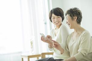 スマートフォンを持って笑顔の母と娘の写真素材 [FYI01624693]