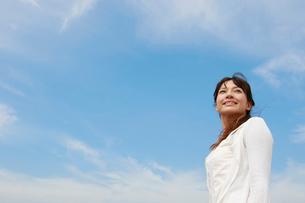 空を見上げる白いワンピースの女性の写真素材 [FYI01625755]