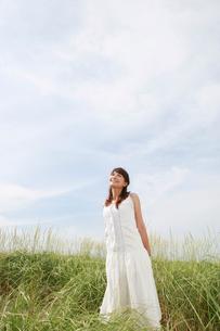 空を見上げる白いワンピースの女性の写真素材 [FYI01625775]