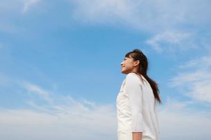 空を見上げる白いワンピースの女性の写真素材 [FYI01626464]