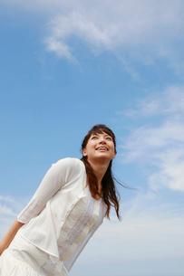 空を見上げる白いワンピースの女性の写真素材 [FYI01626549]