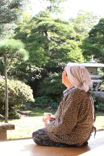 縁側でお茶を飲むおばあちゃんの写真素材 [FYI01628419]