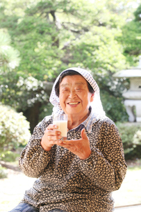 縁側で牛乳を飲むおばあちゃんの写真素材 [FYI01628637]