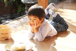 縁側でおにぎりを見つめる男の子の写真素材 [FYI01628683]