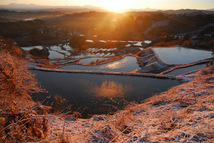 朝日に照らされる冬の棚田棚池の写真素材 [FYI01630735]