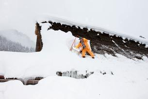 雪の五箇山合掌集落で屋根の雪下ろしの写真素材 [FYI01634971]