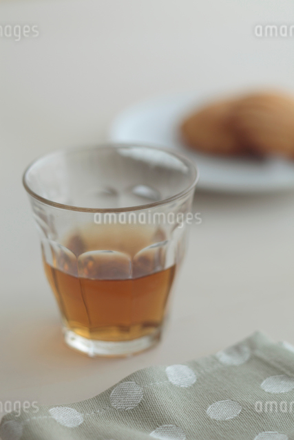 お茶が入ったグラスとマドレーヌの写真素材 [FYI01635028]
